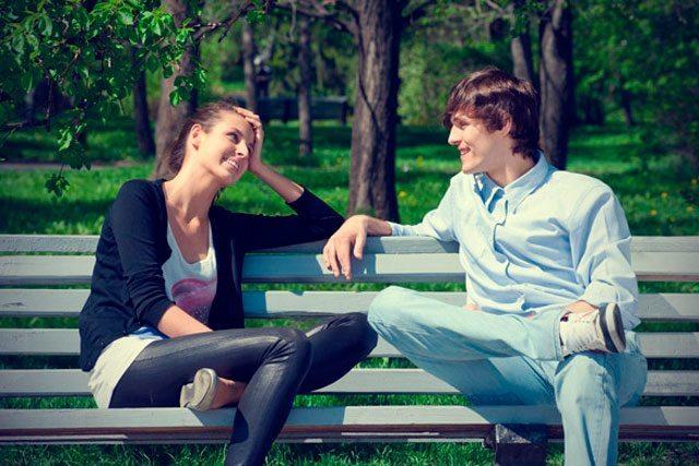 um garoto e uma garota sentados num banco
